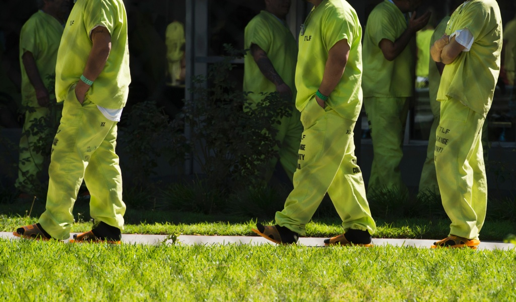 FILE: Men wearing neon-colored jail clothes signifying immigration detainees walk to pick up their lunches at the Theo Lacy Facility, a county jail which houses convicted criminals as well as immigration detainees on March 14, 2017 in Orange, California.