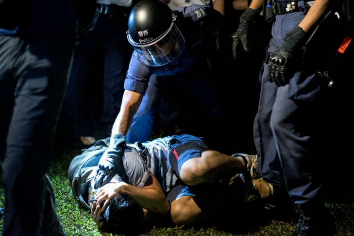 Police officer detains pro-democracy protester in Hong Kong