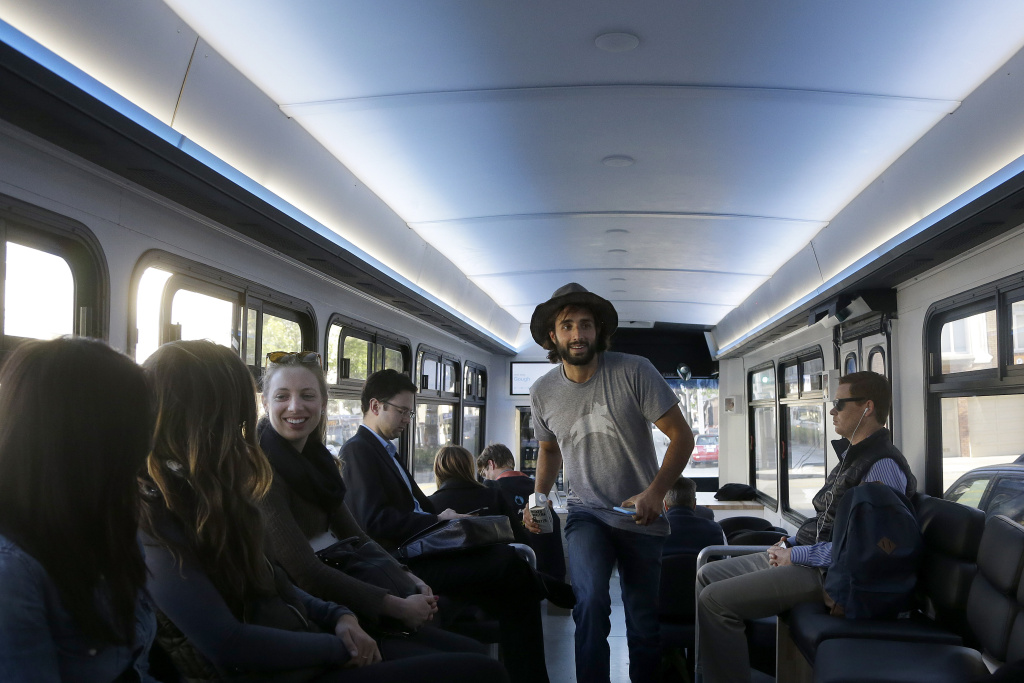 In this April 14, 2015 photo, a Leap employee walks to the back of the bus in San Francisco. Leap, a bus company that offers rides with spacious seating, free Wi-Fi and attendants who deliver snacks, announced on its Facebook page this week that buses would go offline.