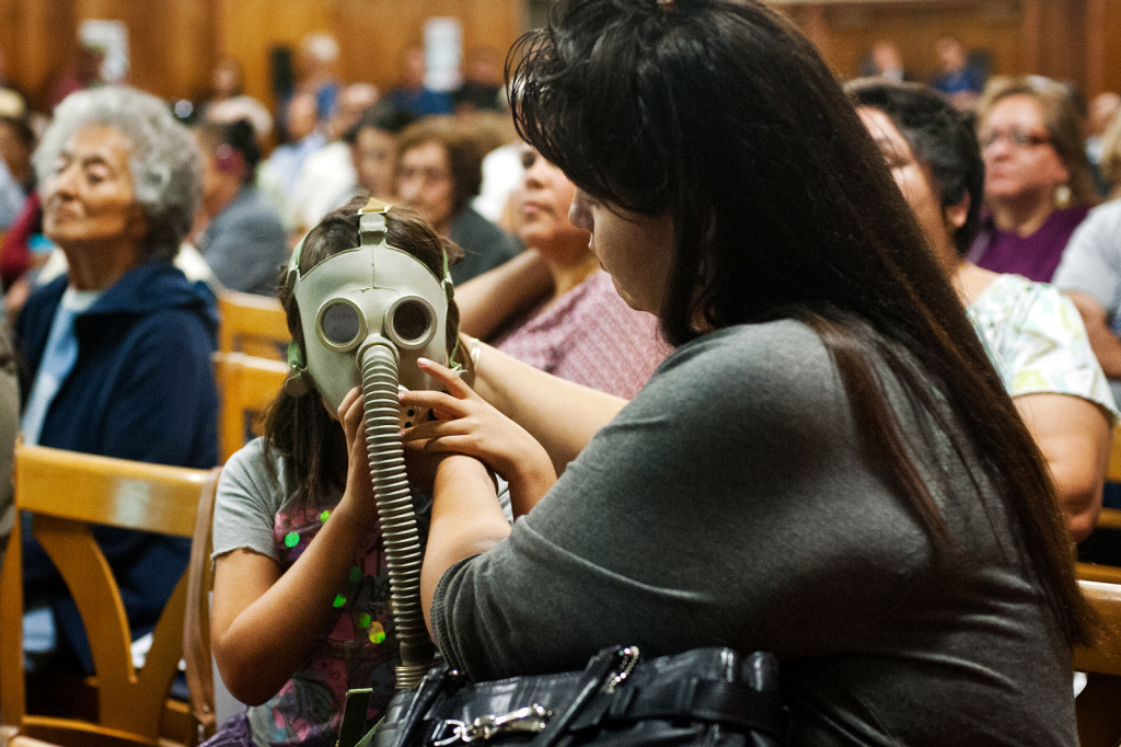 Diana del Pozo-Mora, right, puts a gas mask on her seven-year-old daughter, Josephine Mora, during a town hall meeting at the Resurrection School on Tuesday, Oct. 8 about Exide Technologies, a lead-recycling plant in Vernon.