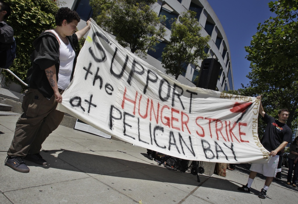 Demonstrators hold up a sign during a rally in front of the State Building in San Francisco, Friday, July 1, 2011 to support prisoners at Pelican Bay State Prison. Inmates in an isolation unit at Pelican Bay State Prison are on a hunger strike to protest conditions that they describe as inhumane. Advocates say several dozen inmates in the Security Housing Unit declined to eat their morning meal on Friday. The unit holds about a third of the 3,100 inmates at the Northern California prison.  (AP Photo/Paul Sakuma)