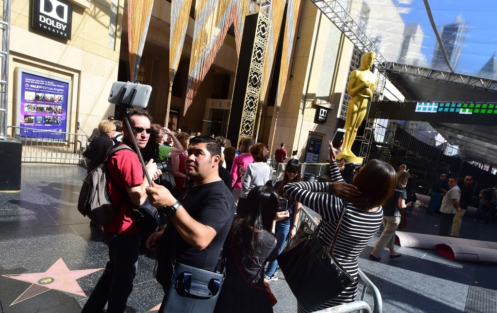 Pedestrians on Hollywood Boulevard snap photos of The Oscar statue in front of the Dolby Theater.