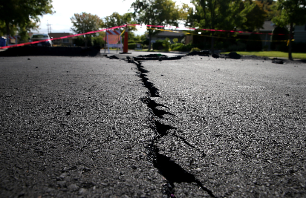 A crack runs down the center of an earthquake-damaged street on August 26, 2014 in Napa, California.  Two days after a 6.0 earthquake rocked the Napa Valley, residents and wineries are continuing clean up operations.