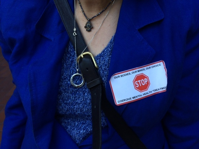 Disability Rights California attorney Ann Menasche wears an anti-Laura's Law sticker at the Orange County Board of Supervisors meeting.