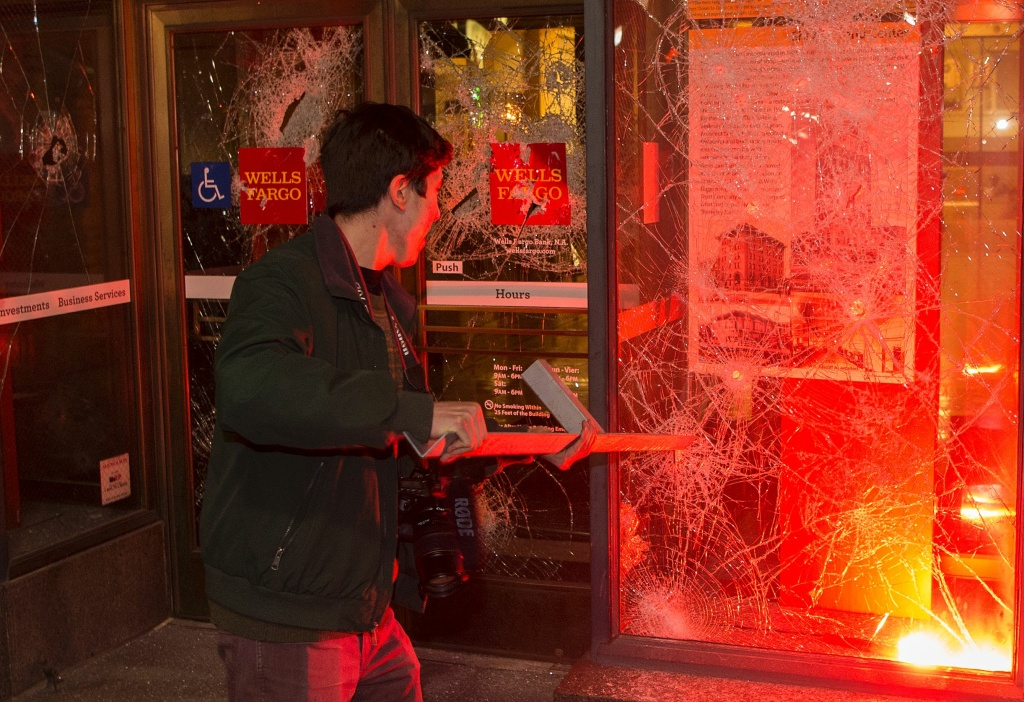 A man pulls a piece of metal out of a window as a flare burns inside a Wells Fargo Bank in Berkeley, on Feb. 1, 2017.