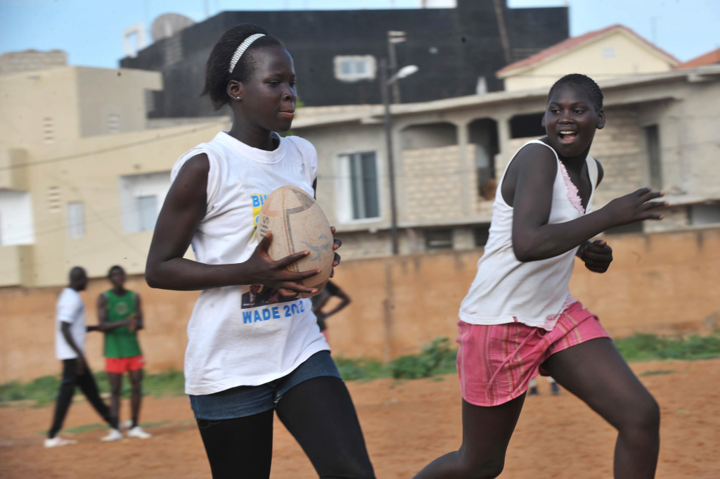 Senegalese girls participate in a rugby match along with other youths at the