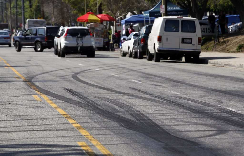 FILE - This Feb. 26, 2015 file photo shows skid marks visible along Plummer Street in the Chatsworth section of Los Angeles following an early-morning illegal street racing crash that killed two bystanders. Henry Gevorgyan, 21, suspected of driving the heavily-modified Mustang that crashed, turned himself in Saturday evening, Feb. 28, 2015. He has been booked on suspicion of murder and is being held on $2 million bail, jail records show. (AP Photo/Nick Ut, File)