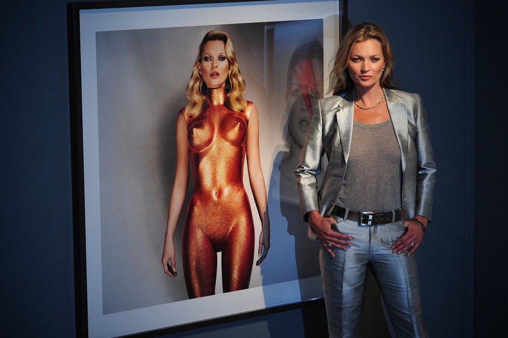 British model Kate Moss poses for photographers next to a photograph entitled 'Body Armour' by Allen Jones, which forms part of the