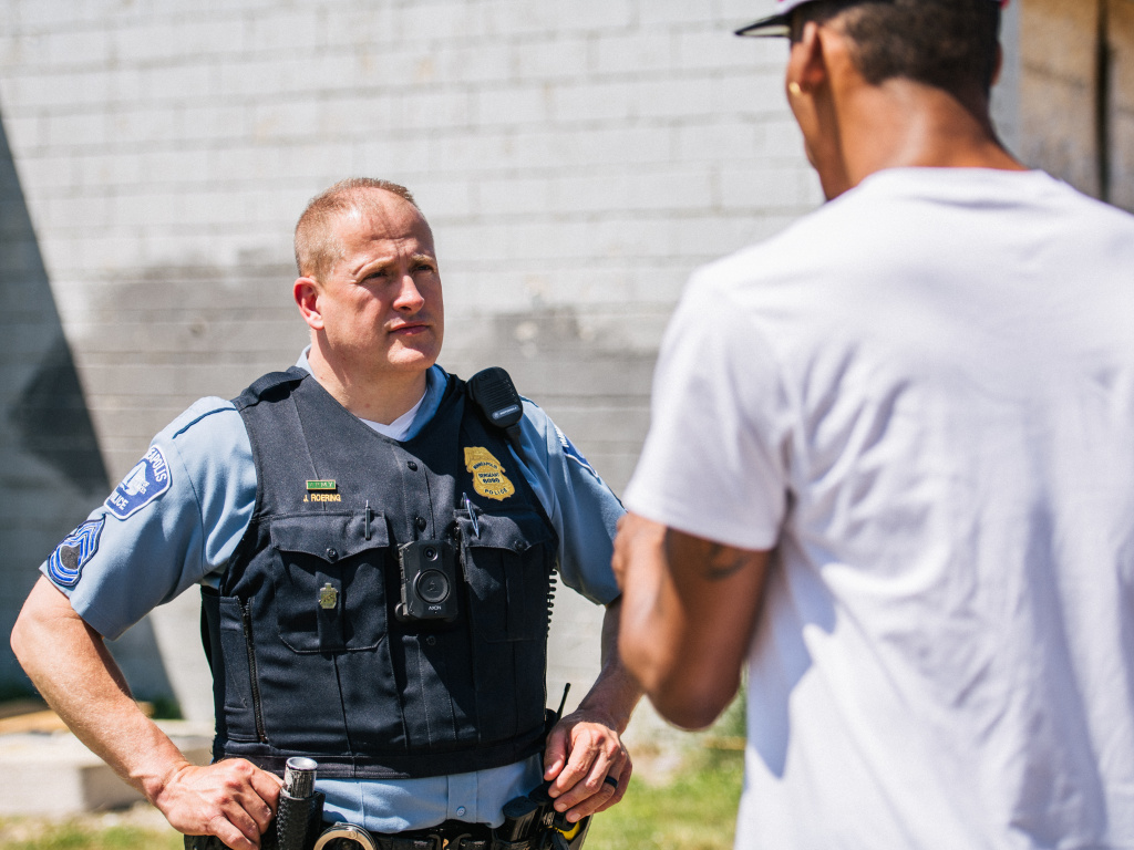 A man speaks with a Minneapolis Police officer at a crime scene on June 16. The Minneapolis City Council voted Thursday to shift $8 million in police funding to other services.