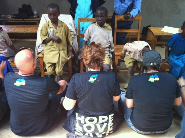 Volunteers helping children with new TOMS shoes. Some critics believe the company's business plan is flawed.