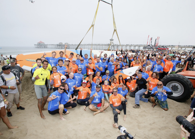 """Sixty-six surfers from around the world ride a custom built 42-foot, 1300 pound surfboard for 12 seconds to break the GUINNESS WORLD RECORDS® for """"Most People Riding a Surfboard at Once"""" on Saturday, June 20, 2015 in Huntington Beach, California.The surfboard, which thousands of spectators filled the Surf City USA shoreline to see, is also expected to break an additional record,"""
