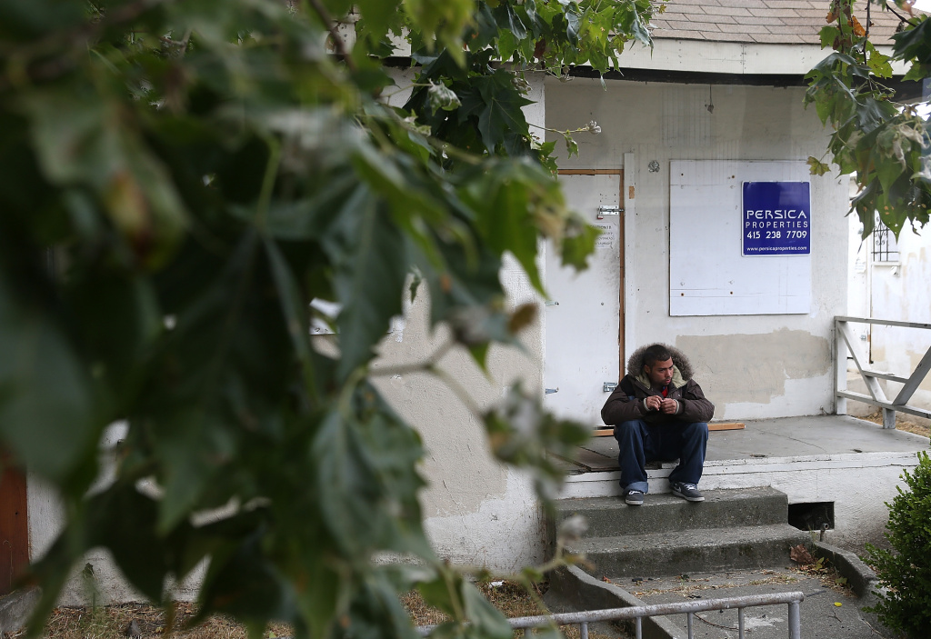 A man sits on the steps of a foreclosed home during a bus tour of foreclosed and blighted properties on July 13, 2012 in Richmond, Calif.  (File Photo by Justin Sullivan/Getty Images)