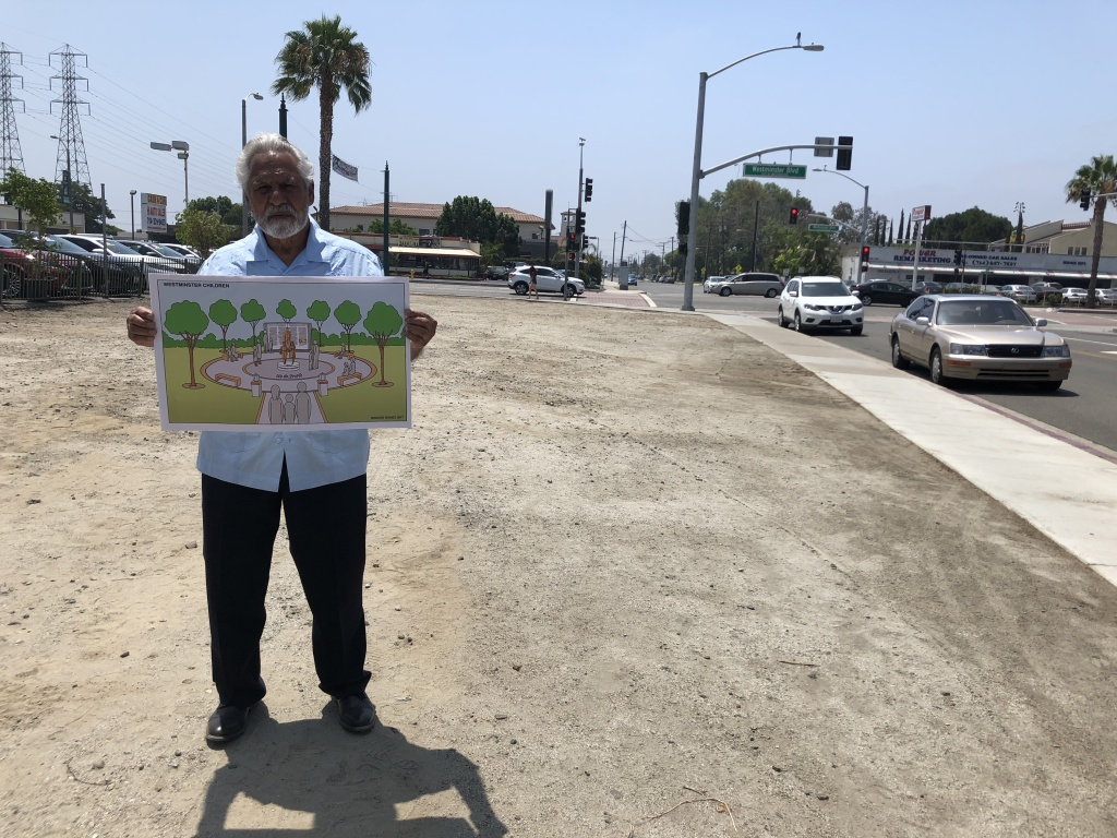 Gonzalo Jr. holds a rendering of the park that will fill the empty space behind him. The park will commemorate his father's victory in eliminating Mexican-only schools in Westminster.
