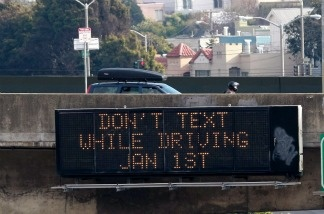 Cars drive by a sign notifying of a new texting while driving law.
