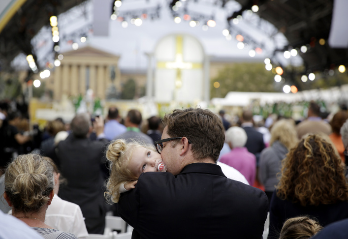 People listen to Pope Francis during a Mass on the Benjamin Franklin Parkway, Sunday, Sept. 27, 2015, in Philadelphia. (AP Photo/Michael Perez)