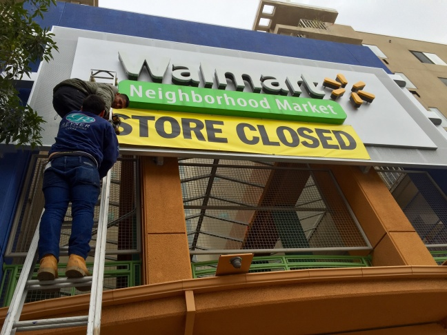 Workers post a sign alerting the neighborhood to Wal-Mart's closure. The store was officially shut down this week.