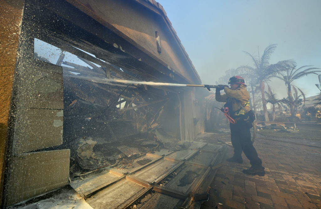 A fireman puts out a fire at a home in the Anaheim Hills neighborhood on October 9, 2017, after the Canyon Fire 2 spread quickly through the area.