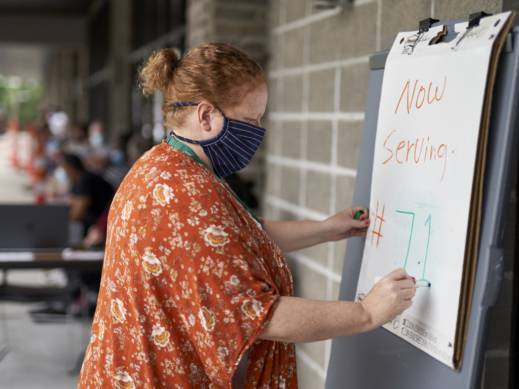 Vickie Gregorio with Heartland Workforce Solutions in Omaha, Neb., updates a whiteboard outside the workforce office as unemployed job seekers wait in line for help. A recent change in federal rules gives some people who have lost their health plan along with their job more than the usual 60 days to sign up for COBRA health coverage.