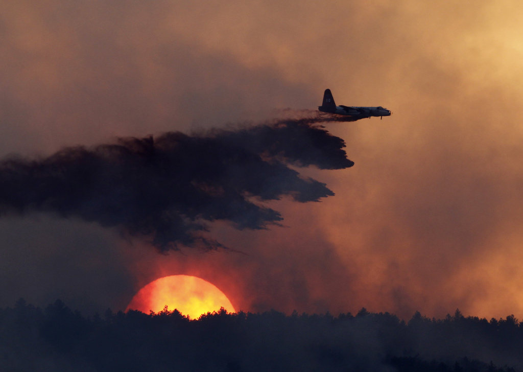 In this Sept. 12, 2010, file photo, a slurry bomber drops fire retardant on a burning ridge as the sun sets behind it as a wildfire burns west of Loveland, Colo. Human-caused global warming is to blame for bigger wildfires, according to at least three different studies in the past three months.