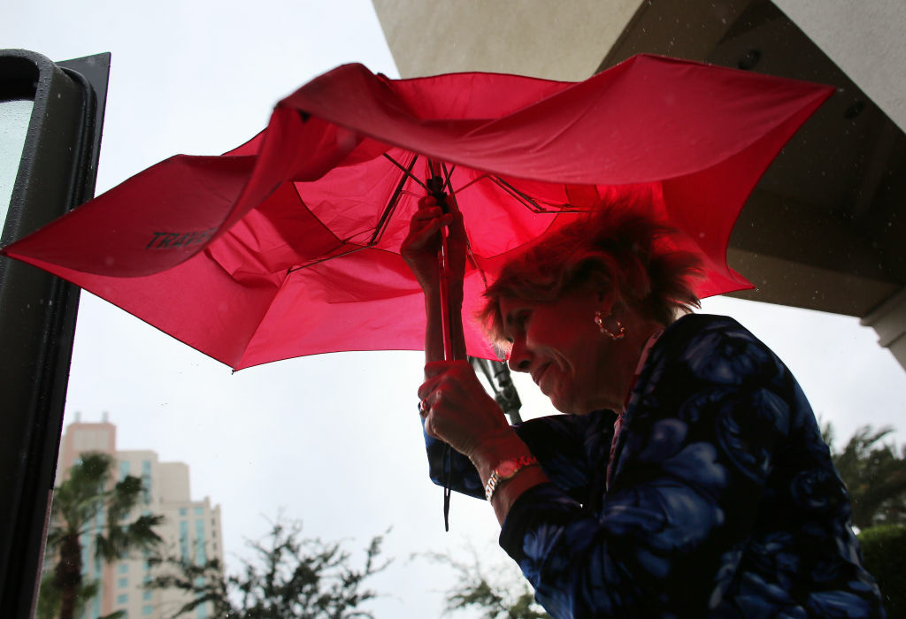 TAMPA, FL - AUGUST 27:  A woman opens her umbrellaas it rains before the start of the abbreviated first day of the Republican National Convention outside the Tampa Bay Times Forum on August 27, 2012 in Tampa, Florida. The RNC is scheduled to convene today, but will hold its first full session tomorrow after being delayed due to Tropical Storm Isaac.  (Photo by Win McNamee/Getty Images)