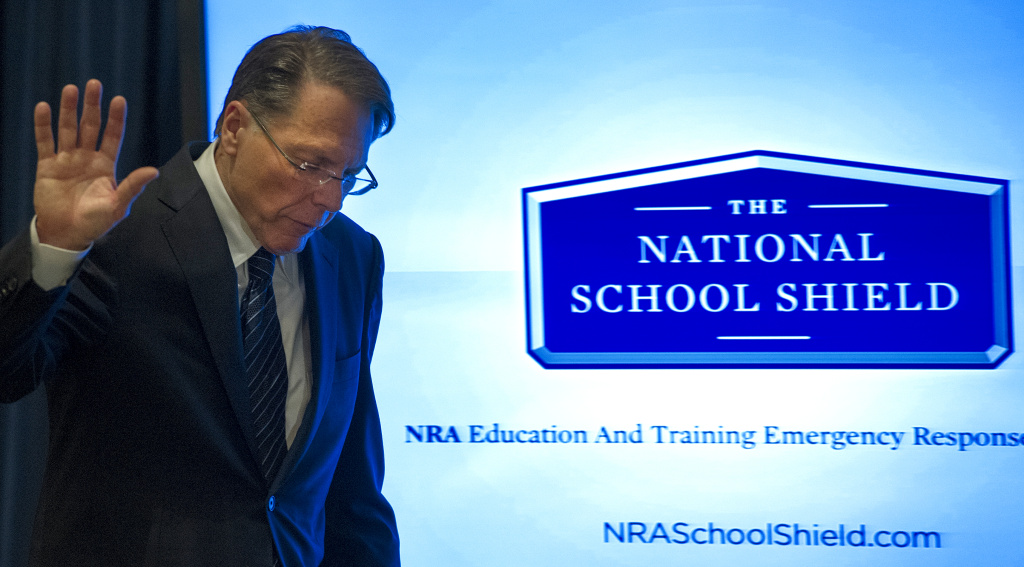 National Rifle Association (NRA) Executive Vice President Wayne LaPierre waves off questions from the media as he walks by a video screen illustrating the NRA's proposed National School Shield, December 21, 2012, in Washington, DC, on the one week anniversary of the Sandy Hook Elementary School shootings in Newtown, Connecticut. The United States' most powerful pro-gun lobbying group, the National Rifle Association, called Friday for armed police or security guards to be deployed to every school in the country.