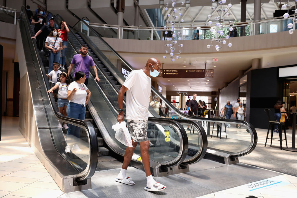 Consumers exit an escalator as they return to retail shopping at the Arrowhead Towne Center on June 20, 2020 in Glendale, Arizona.