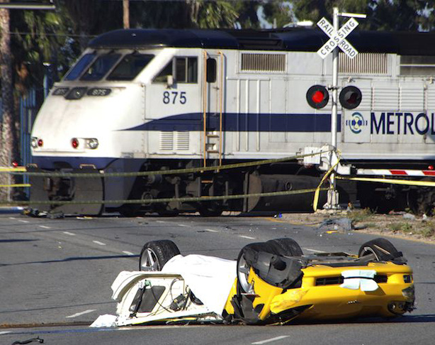 A commuter train passes behind the wreckage of 2007 Corvette after the car crashed early Thursday, May 6, 2010, killing four people in Los Angeles' San Fernando Valley. The wreck, at about 12:05 a.m. Thursday, left car and body parts scattered along a half-mile stretch of the road.