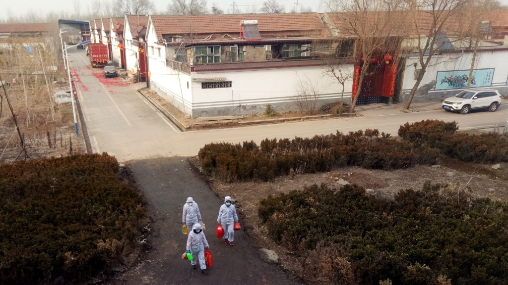 More than 17,000 people have been diagnosed with a new coronavirus since it was identified in December. Here, volunteers in protective suits deliver daily supplies to people who are under self-quarantine at a village in Shandong province, China.