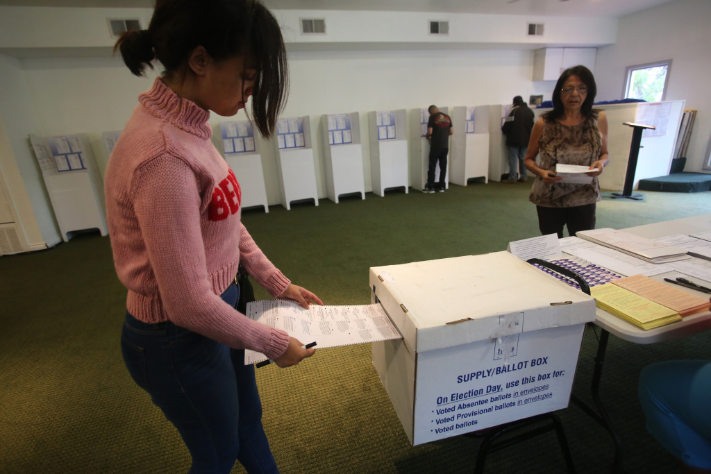 California primary voter Yanira Michelle slips her ballot into the ballot box at a polling station June 7, 2016 in San Diego, California. / AFP / Bill Wechter