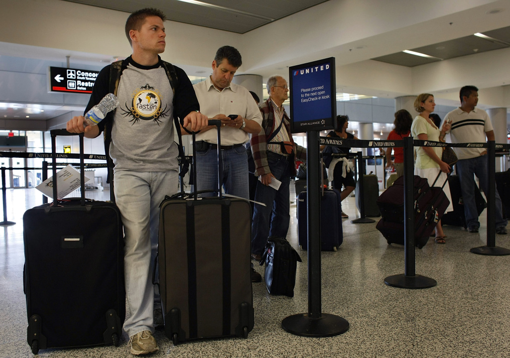Passengers wait to check in with their baggage at the United Airlines counter at the Miami International Airport June 12, 2008 in Miami, Florida.
