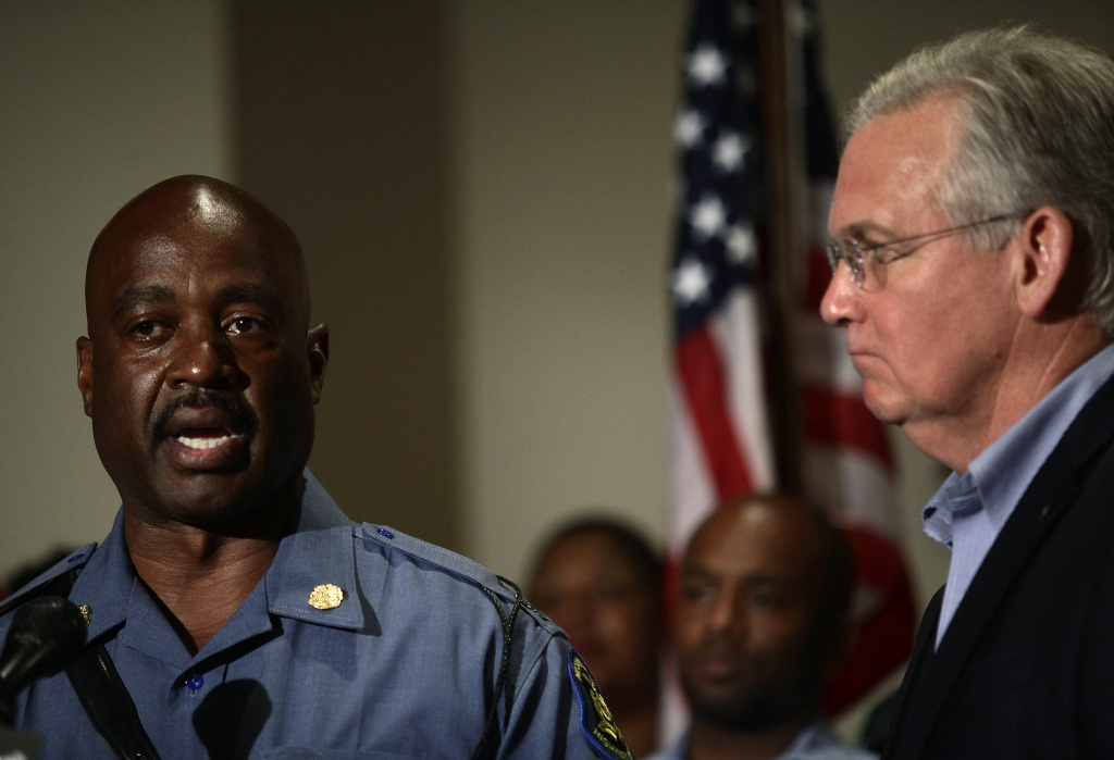 Missouri State Highway Patrol Captain Ronald Johnson speaks about the shooting death of 18 year-old Michael Brown as Missouri Governor Jay Nixon, right, looks on during a news conference August 16, 2014 in Ferguson, Missouri. Johnson and Nixon imposed a 12am curfew along with Missouri State Highway Patrol Captain Ronald Johnson for demonstrators continuing to protest the killing of Brown, who was shot and killed last week by Ferguson Police Officer Darren Wilson after being suspected in taking part in a robbery at a convenience store.