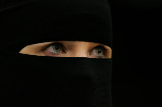 A woman wearing a niqab veil listens during a seminar organised by the women's chapter of Hizb-ut-Tahrir Britain, to challenge the remarks made by Jack Straw and other British ministers against the veil on October 14, 2006 in London, England.