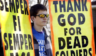 A member of Westboro Baptist Church of Topeka, Kansas, protests outside Holy Ghost Church during the funeral service for Marine Lance Cpl. Philip Martini April 19, 2006 in South Holland, Illinois.