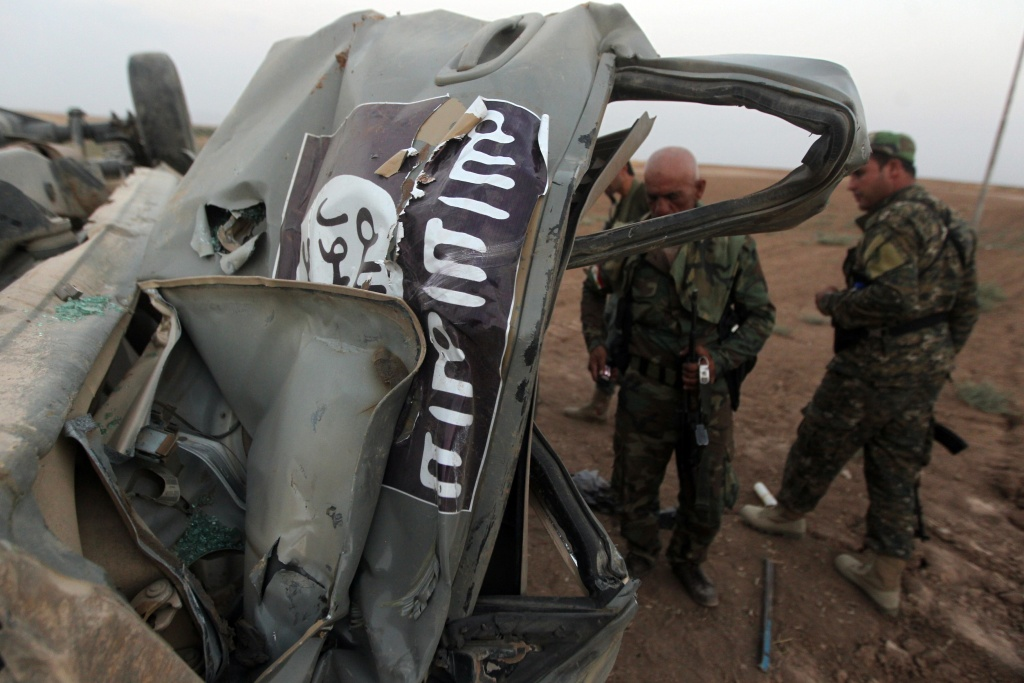 Peshmerga fighters inspect the remains of a car, bearing an image of the trademark jihadist flag, which belonged to Islamic State (IS) militants after it was targeted by an American air strike in the village of Baqufa, north of Mosul, on August 18,2014. Kurdish peshmerga fighters backed by federal forces and US warplanes pressed a counter-offensive Monday against jihadists after retaking Iraq's largest dam, as the United States and Britain stepped up their military involvement.