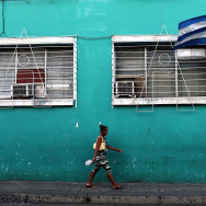 A woman walks under a Cuban flag in Santiago de Cuba. The Obama administration has relaxed rules for travel to Cuba. But U.S. travelers must still go for a specific purpose.