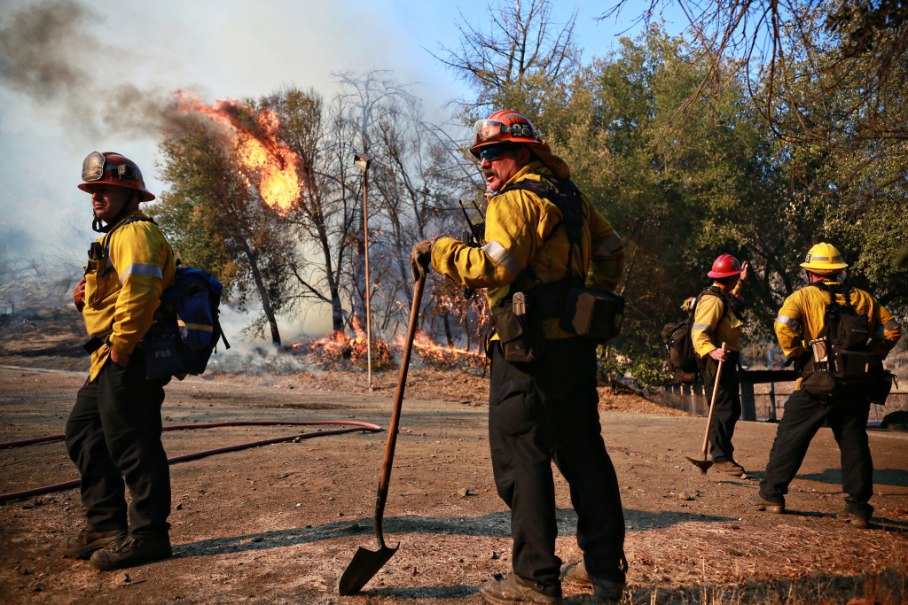 MALIBU, CA - NOVEMBER 11: Firefighters battle a blaze at the Salvation Army Camp on November 10, 2018 in Malibu, California. The Woolsey fire has burned over 70,000 acres and has reached the Pacific Coast at Malibu as it continues grow.  (Photo by Sandy Huffaker/Getty Images)