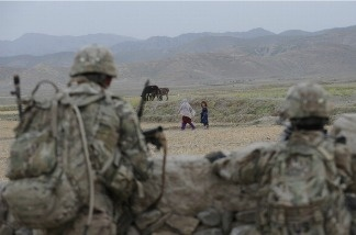 US soldiers from Viper Company (Bravo), 1-26 Infantry watch as young girls walk past them during a patrol in the east of Afghanistan on June 22, 2011.