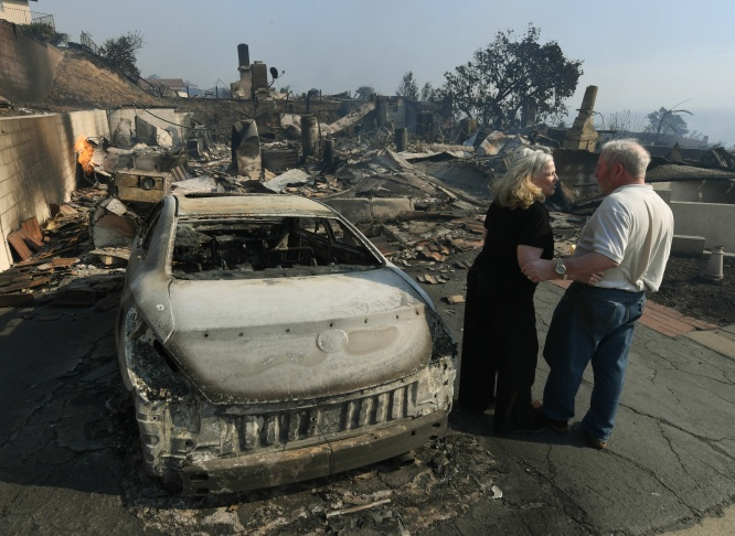 Michael and Vonea McQuillam stand beside the ruins of their Ventura home on Dec. 5, 2017. It was destroyed by the Thomas fire.