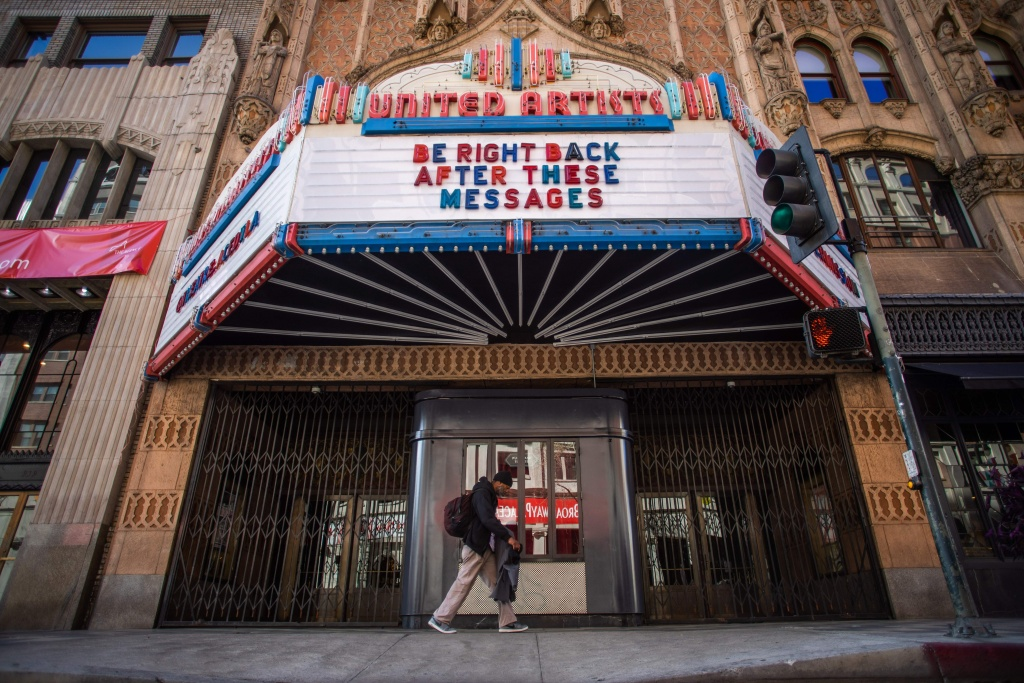 A man walks by the closed United Artists theater in Downtown Los Angeles during the novel coronavirus (COVID-19) outbreak.