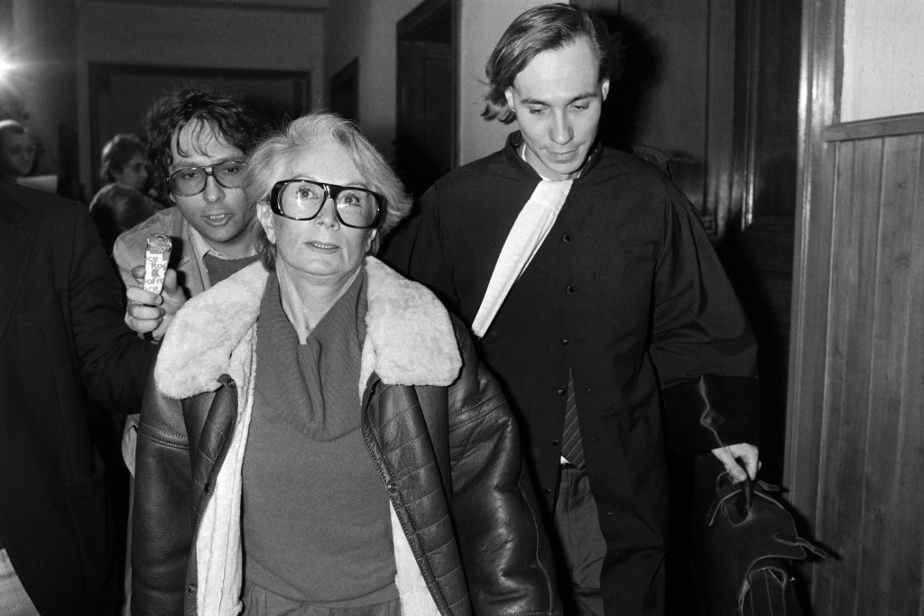 A file picture taken on January 20, 1986 shows Fernande Grudet also known as Madame Claude (L) walking with her lawyer Bruno Simonetta at the Court of Cahors during her trial.