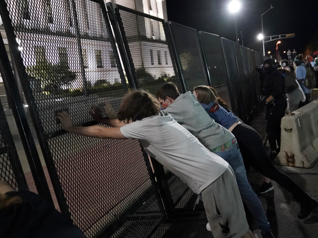 Protesters attempt to topple a fence outside the Kenosha County Courthouse late Tuesday in Kenosha, Wis. Protests continued following the police shooting of Jacob Blake Sunday.