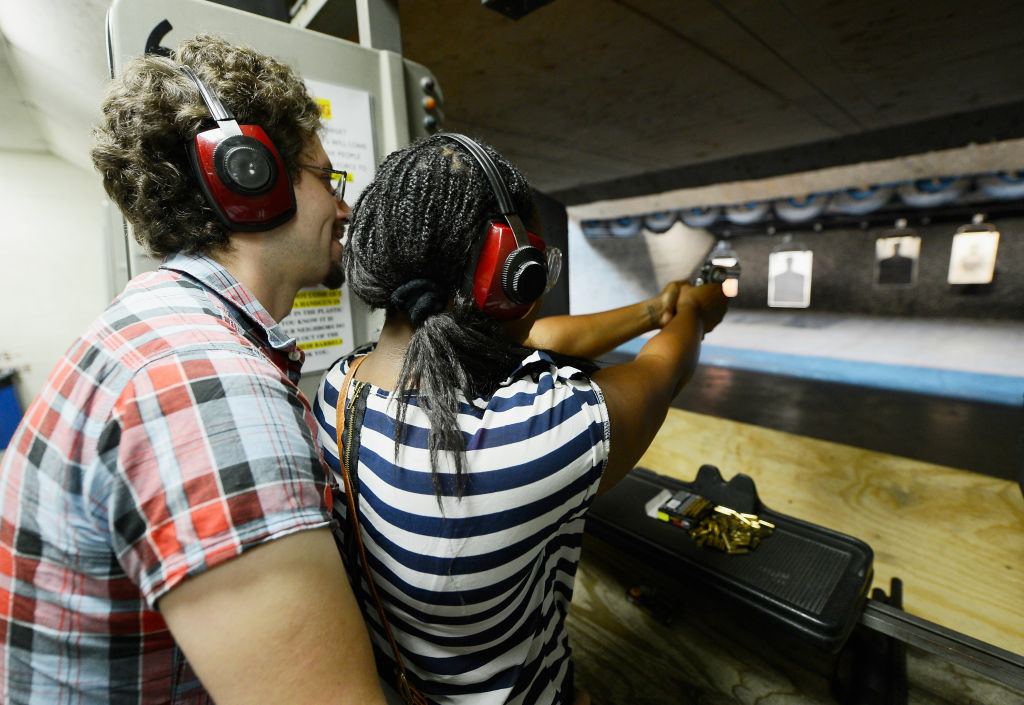 Domenic Lether teaches his girlfriend Ngozi Ogbeni how to shoot a Smith & Wesson .357 magnum revolver at a target range at the Los Angeles Gun Club on December 7, 2012 in Los Angeles, California.