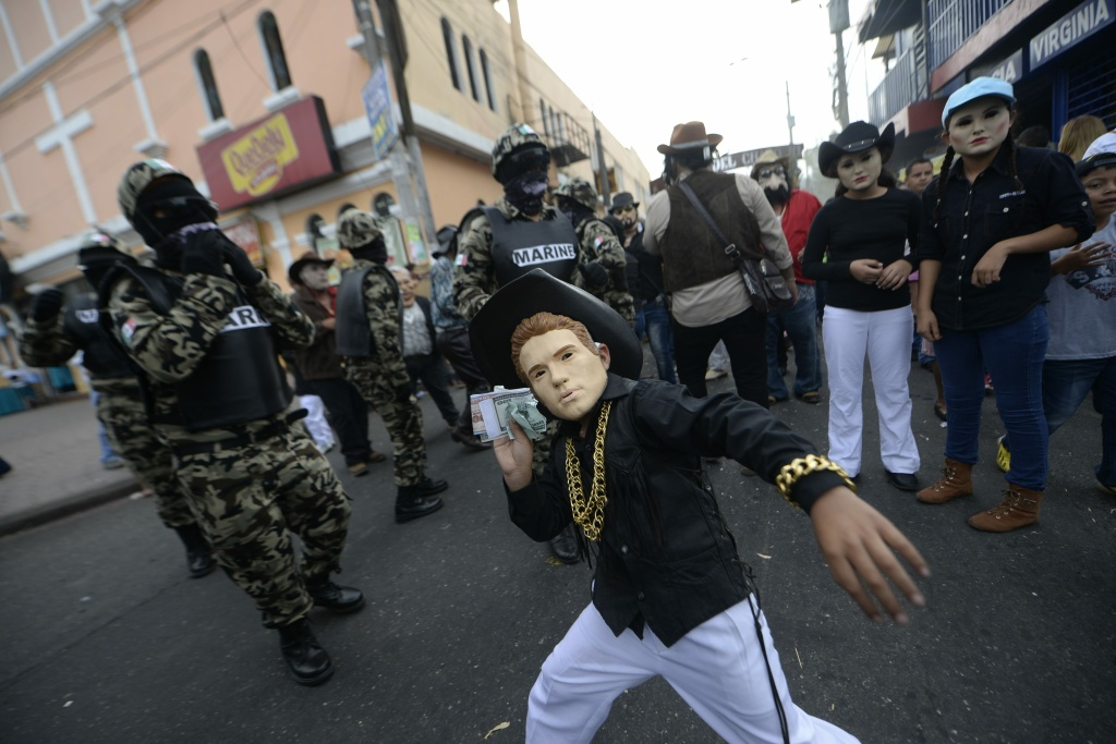 A reveler dressed as a drug trafficker takes part in the traditional