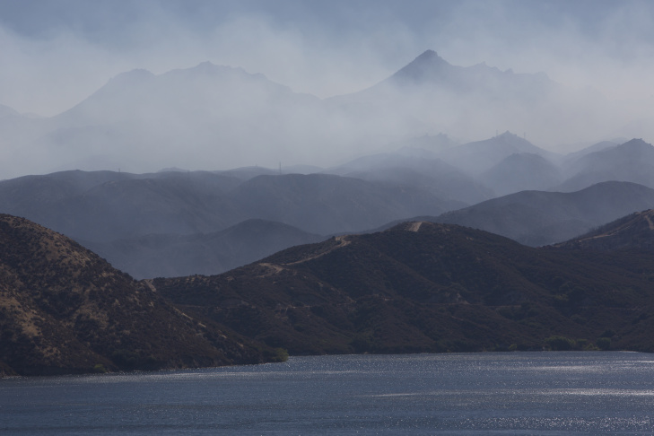 Smoke from the Pilot fire blows over the hills above Silverwood Lake in California on August 9th, 2016.