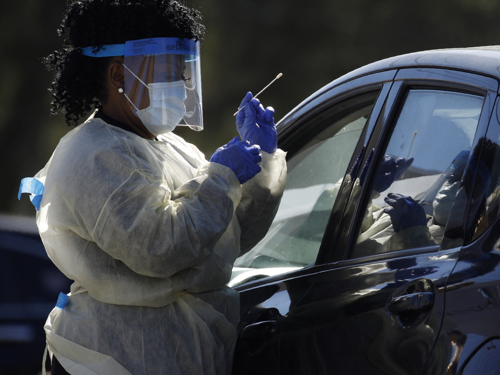 A health care worker with the UNLV School of Medicine tests a patient for the coronavirus at a drive-thru testing site in Las Vegas.