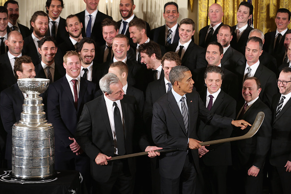 File: Los Angeles Kings Head Coach Darryl Sutter (L) presents President Barack Obama with a silver hockey stick as Obama hosted the National Hockey League champions in the East Room of the White House Feb. 2, 2015 in Washington, D.C.