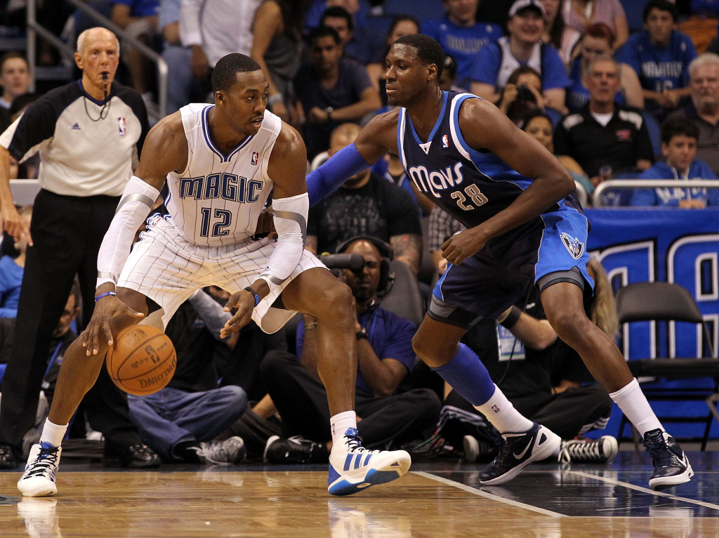 Dwight Howard #12 of the Orlando Magic drives against Ian Mahinmi #28 of the Dallas Mavericks during the game at Amway Center on March 30, 2012 in Orlando, Florida.