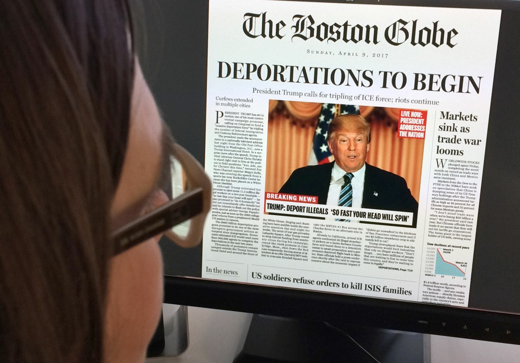 This April 10, 2016 photo taken in Washington shows a woman reading an online version of a mockup of what a frontpage might look like should Republican frontrunner Donald Trump win the presidency, as it condemned his