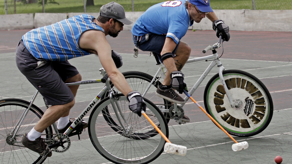 Jacob Newborn takes a shot past Lodewijk Broekhuizen, left, during a bike polo practice session in Milwaukee.
