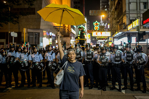 A pro-democracy activist holds a yellow umbrella in front of a police line on a street in Mongkok district on November 25, 2014 in Hong Kong.